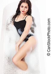 young sexy girl in a bath with foam