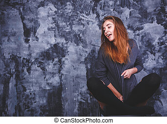 young sexy girl in a stylish jacket is sitting on chair