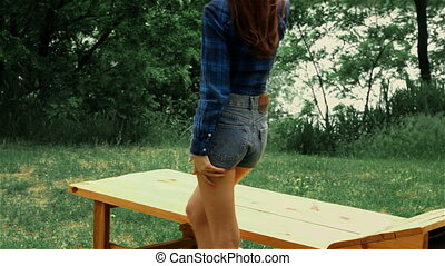 young sexy girl in denim shorts and shirt sits on the bench...