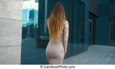 girl in skirt with beautiful buttocks and long hair goes around the city and talks on a mobile phone