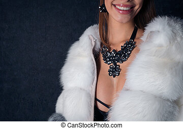 Young sexy girl smiling in a fur coat with beautiful accessories insulated on dark