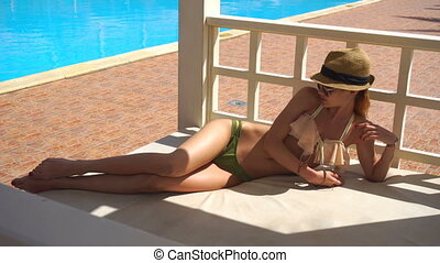 young sexy girl with glasses and hat tans in the Sun in a swimsuit