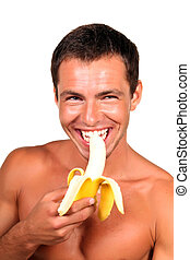 Young sexy handsome man eating banana