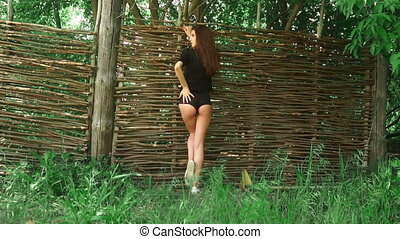 young sexy lady touching her buttocks and looking aside at the fence outdoors
