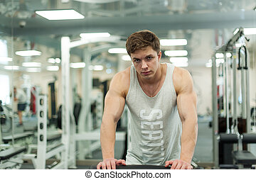 Young sexy male bodybuilder athlete, trains in the gym, using sports equipment and fitness equipment to improving health and beauty of the body