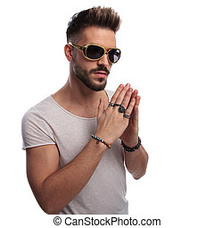 young sexy man in sunglasses is praying