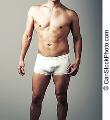 young sexy man posing in white pants.