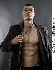 Young sexy man with athletic body posing on black...