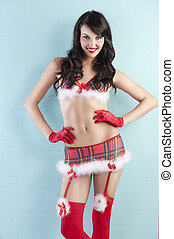 young sexy pinup in a red christmas dress with very short skirt and stocking and bra with glove over green, her hands are placed on the hips