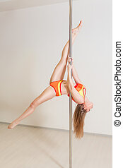 Young sexy pole dance woman stretching