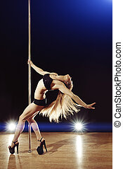 Young sexy pole dance woman with fluttering hair performing...