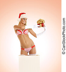 Young sexy Santa gets out of a box over pink background