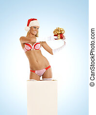Young sexy Santa gets out of a box over blue background