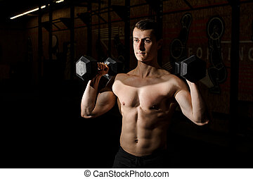 Young sexy shirtless man practicing crossfit in a gym