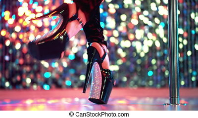 Young sexy striptease dancer moving in high heels shoes with rhinestones on stage with pylone in strip night club, Pole dancing. Shining background. Dance, temptation concept.