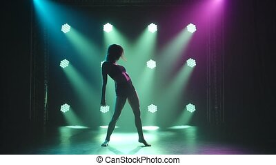 Young sexy woman dancing contempt in black lingerie. Modern romantic choreography on a black background with spotlights in a smoky studio. Silhouette. Slow motion.