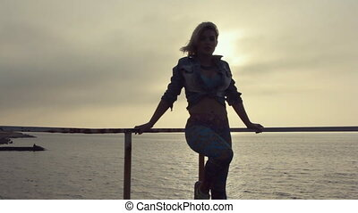 Young sexy woman dancing dancehall on the pier near the sea at a sunset