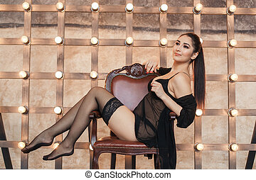 Young sexy woman in stockings on chair