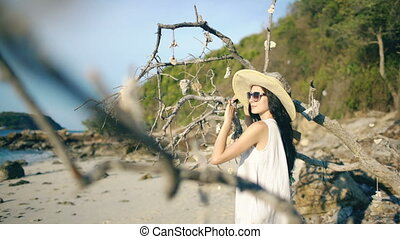 Young sexy woman in sunglasses and hat smiling and posing near tree at beautiful tropical beach