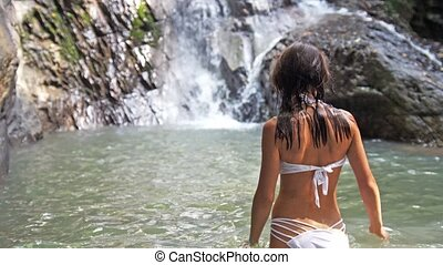 Young sexy woman in white bikini enters in a pond swims in tropical waterfall. slow motion.