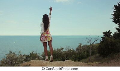Young sexy woman is waving to the ocean from the top of...