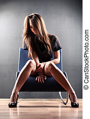 Young sexy woman on a chair