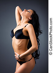 Young sexy woman. On dark wall background.