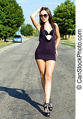 Young sexy woman walking on the road