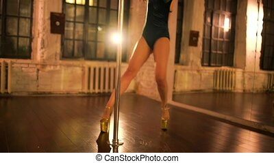Young sexy woman pole dancing at night.