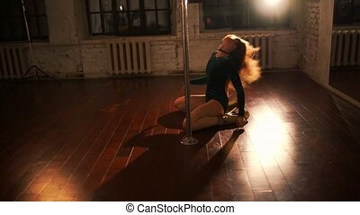 Young sexy woman pole dancing at night