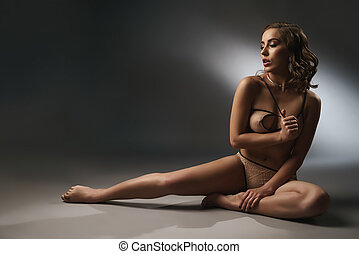 Young sexy woman posing in beige lingerie