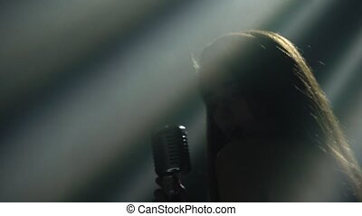 Young sexy woman profile with beautiful face and lips. Female singer sings into a vintage microphone in the studio. Silhouette in the spotlight. Close up.