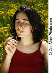 Young sexy woman smelling a flower