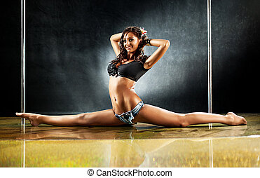 Young sexy woman dancer on wall background.