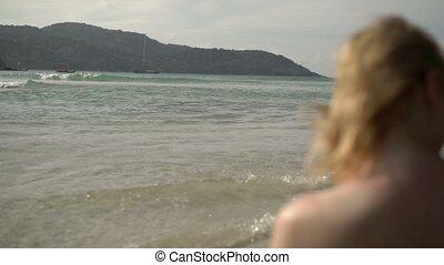 Young sexy woman sunbathing in sea