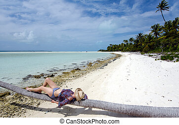 Young, sexy woman sunbathing on deserted tropical island