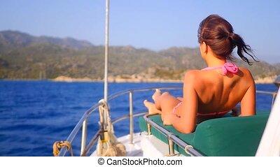 Young sexy woman sunbathing on luxury yacht