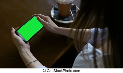 Young sexy woman surfing the internet on her green screen smart phone at lunch break in a pub