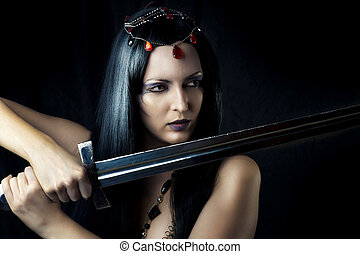 Young sexy woman warrior holding sword