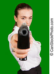 Young sexy woman with gun isolated on Green