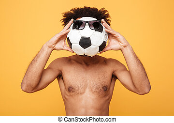 Young shirtless african man covering head with a foot ball -...