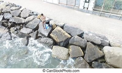 Young shirtless athletic man sitting on rock by sea