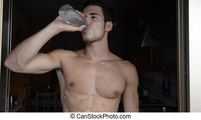 Young shirtless man drinking water from plastic bottle