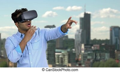 Young shocked man wearing vr glasses outdoor. Scared surprised man in vr headset pointing with index finger upward. City skyscrapers in the background.