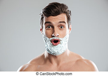 Young shocked man with shaving foam on face