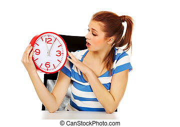 Young shocked teenage woman looking at clock