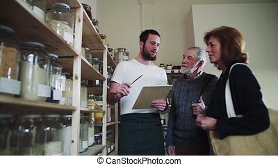 Young shop assistant serving a senior couple in a zero waste shop.