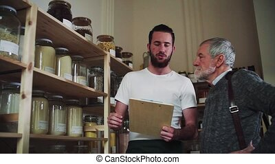 Young shop assistant serving a senior man in a zero waste...