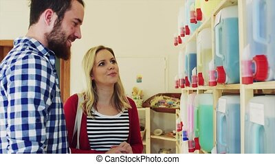 Young shop assistant serving an attractive woman in a zero waste shop.