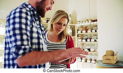 Young shop assistant with tablet serving an attractive woman in a zero waste shop.
